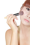 Beautiful woman applying powder on cheek with brush Stock Photo