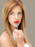 Beautiful woman applying red lipstick Stock Images