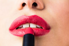 Beautiful woman applying red lipstick on lips against black background Stock Photography