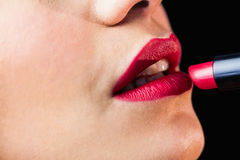 Beautiful woman applying red lipstick on lips against black background Royalty Free Stock Photos