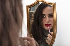 Beautiful woman applying red lipstick. Using a handheld gold framed vintage mirror with focus to her reflection in the glass Royalty Free Stock Photos
