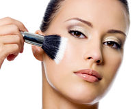 Beautiful woman applying rough on cheek Royalty Free Stock Image