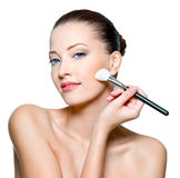 Beautiful woman applying  rough on cheek Stock Photography