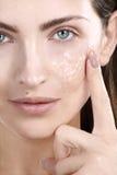 Beautiful woman applying scrub treatment on face. Closeup Royalty Free Stock Photos
