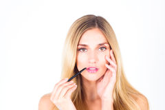 Beautiful woman applying shine on her lips with a brush and touching her face Stock Images
