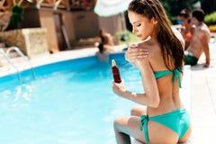 Beautiful woman applying skin uv protection