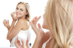 Beautiful woman while  applying some facial cream on her nose Stock Image
