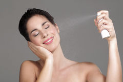 Beautiful woman applying spray water on face. On neutral background Stock Image