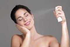 Beautiful woman applying spray water on face Stock Image