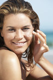 Beautiful Woman Applying Sunscreen On Face Royalty Free Stock Images