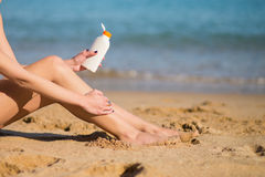 Beautiful woman applying sunscreen on her legs Stock Photo
