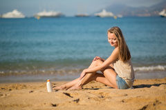 Beautiful woman applying sunscreen on her legs Royalty Free Stock Images