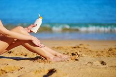 Beautiful woman applying sunscreen on her legs Stock Photos