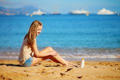 Beautiful woman applying sunscreen on her legs Royalty Free Stock Image