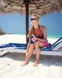 Beautiful woman applying suntan lotion Stock Photos