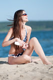 Beautiful woman applying suntan lotion at beach Royalty Free Stock Photos