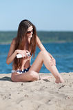 Beautiful woman applying suntan lotion at beach Royalty Free Stock Photo
