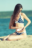 Beautiful woman applying suntan lotion at beach Stock Photo