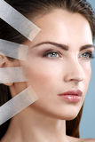 Beautiful woman applying tape lifting treatment on face Royalty Free Stock Photos