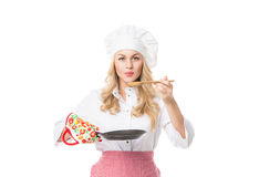 Beautiful woman in apron and hat blowing on spoon with hot food Stock Images