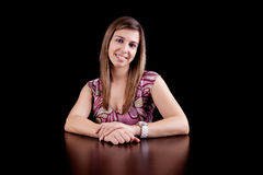 Beautiful Woman with arms crossed. Portrait of a beautiful young woman smiling, with her arms crossed, wearing a pink dress on black background. Studio shot stock photos
