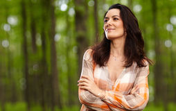 Beautiful woman with arms folded in a forest Stock Photography