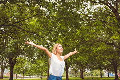 Beautiful woman with arms raised in park Royalty Free Stock Photography