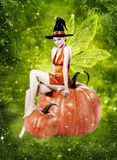 Beautiful woman as halloween witch. Beautiful woman as witch sitting on pumpkin - halloween portrait royalty free stock images