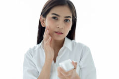 A beautiful woman asian using a skin care product, moisturizer o. R lotion taking care of her dry complexion. Moisturizing cream in female hands Royalty Free Stock Photo