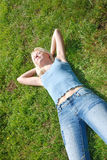 A beautiful  woman asleep in a grassy field Royalty Free Stock Image