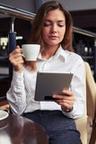 Beautiful woman attentively reading latest news on tablet Royalty Free Stock Photo