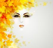 Beautiful woman in autumn circle of leaves. Beautiful woman face is in autumn circle of yellow and orange leaves on the light background Stock Images
