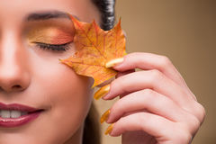 The beautiful woman in with autumn dry leaves. Beautiful woman in with autumn dry leaves royalty free stock image