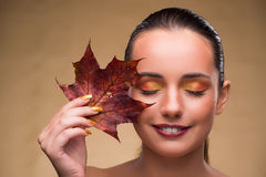 The beautiful woman in with autumn dry leaves Stock Images