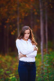 Beautiful woman in the autumn forest. Young brunette girl royalty free stock image