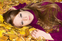 Beautiful woman on autumn leaves Royalty Free Stock Photography