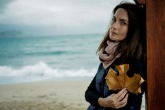 Beautiful Woman with Autumn Leaves against the sea in rainy day Stock Images