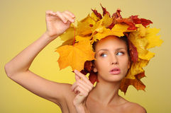 Beautiful woman with autumn leaves on yellow Royalty Free Stock Image