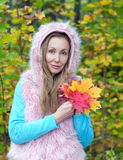 Beautiful woman in autumn park with an armful of maple leaves. The beautiful woman in autumn park with an armful of maple leaves royalty free stock photography