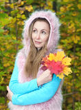 Beautiful woman in autumn park with an armful of maple leaves. The beautiful woman in autumn park with an armful of maple leaves royalty free stock images