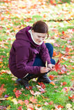 Beautiful woman in the autumn park collects leaves Stock Photos