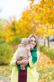 The beautiful woman in the autumn park holding teddy bear Stock Photography
