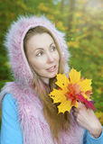 The beautiful woman in autumn park with maple leaves.  royalty free stock photography