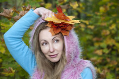 The beautiful woman in autumn park with maple leaves.  royalty free stock photo