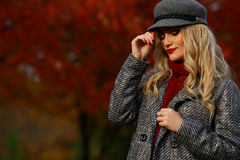 Beautiful woman in autumn park. Red maple garden background. Copy space Stock Images