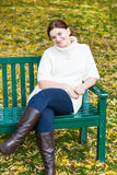 Beautiful woman in the autumn park sitting on bench Stock Photos