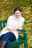Beautiful woman in the autumn park sitting on bench Stock Photography
