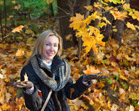 Beautiful woman in autumn park throws up red maple leaves Royalty Free Stock Photography