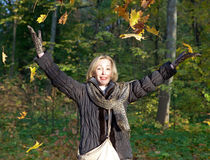 Beautiful woman in autumn park throws up red maple leaves Royalty Free Stock Photos