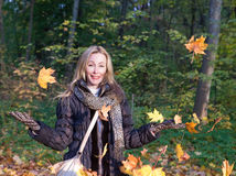 Beautiful woman in autumn park throws up red maple leaves. The beautiful woman in autumn park throws up red maple leaves royalty free stock photography